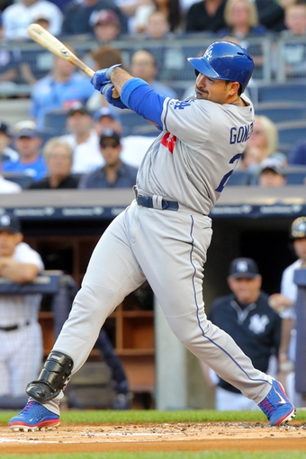 Jun 19, 2013; Bronx, NY, USA; Los Angeles Dodgers first baseman Adrian Gonzalez (23) hits an RBI single against the New York Yankees during the first inning of a game at Yankee Stadium. Mandatory Credit: Brad Penner-USA TODAY Sports