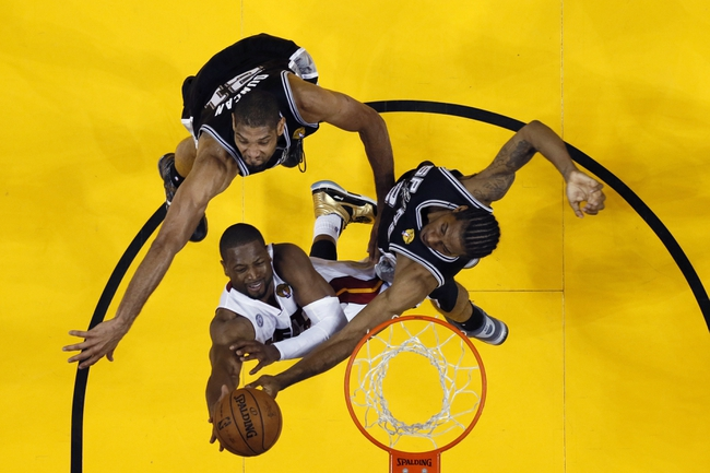 Jun 20, 2013; Miami, FL, USA; Miami Heat shooting guard Dwyane Wade (3) shoots against San Antonio Spurs power forward Tim Duncan (back) and shooting guard Danny Green (right) during game seven in the 2013 NBA Finals at American Airlines Arena. Mandatory Credit: Mike Erhmann-Getty/Pool Photo via USA TODAY Sports