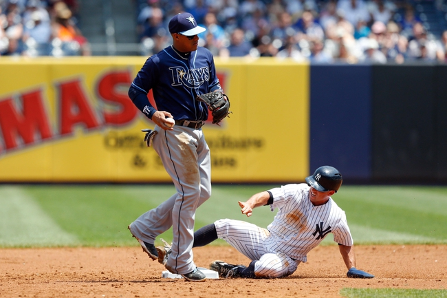Jun 22, 2013; Bronx, NY, USA;  Tampa Bay Rays shortstop Yunel Escobar (11) forces out New York Yankees center fielder Brett Gardner (11) during the third inning at Yankee Stadium.  Mandatory Credit: Anthony Gruppuso-USA TODAY Sports