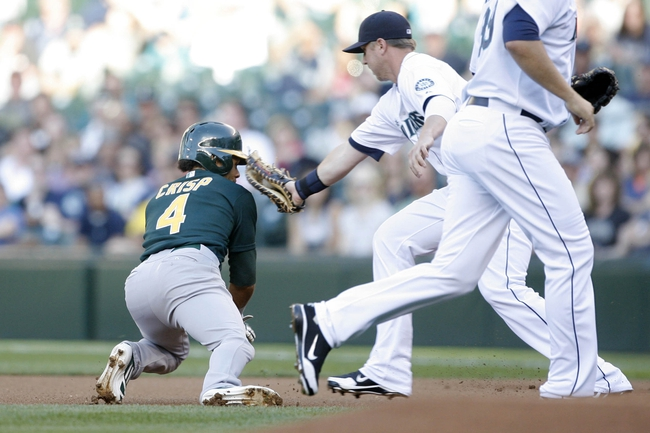 Jun 22, 2013; Seattle, WA, USA; Oakland Athletics designated hitter Coco Crisp (4) is tagged out by Seattle Mariners first baseman Justin Smoak (17) during the first inning at Safeco Field. Mandatory Credit: Joe Nicholson-USA TODAY Sports