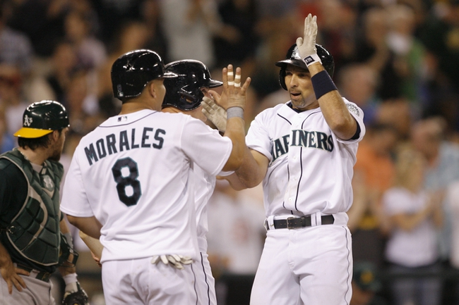 Jun 22, 2013; Seattle, WA, USA; Seattle Mariners left fielder Raul Ibanez (28) is congratulated at home after hitting a three-run homer against the Oakland Athletics during the seventh inning at Safeco Field. Mandatory Credit: Joe Nicholson-USA TODAY Sports