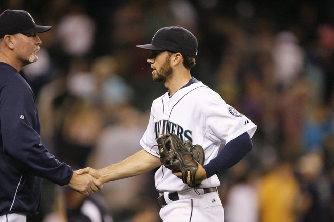 Jun 22, 2013; Seattle, WA, USA; Seattle Mariners second baseman Nick Franklin (20) shakes hands with manager Eric Wedge (22) after the final out of a 7-5 victory against the Oakland Athletics at Safeco Field. Mandatory Credit: Joe Nicholson-USA TODAY Sports