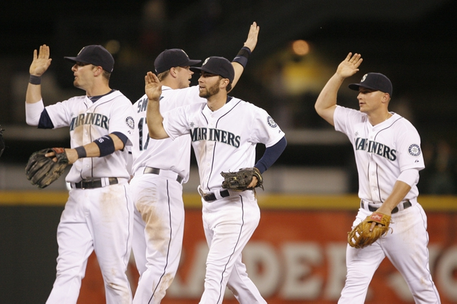 Jun 22, 2013; Seattle, WA, USA; Seattle Mariners shortstop Brendan Ryan (26, left), first baseman Justin Smoak (17), second baseman Nick Franklin (20) and third baseman Kyle Seager (15) celebrate after the final out of a 7-5 victory against the Oakland Athletics at Safeco Field. Mandatory Credit: Joe Nicholson-USA TODAY Sports