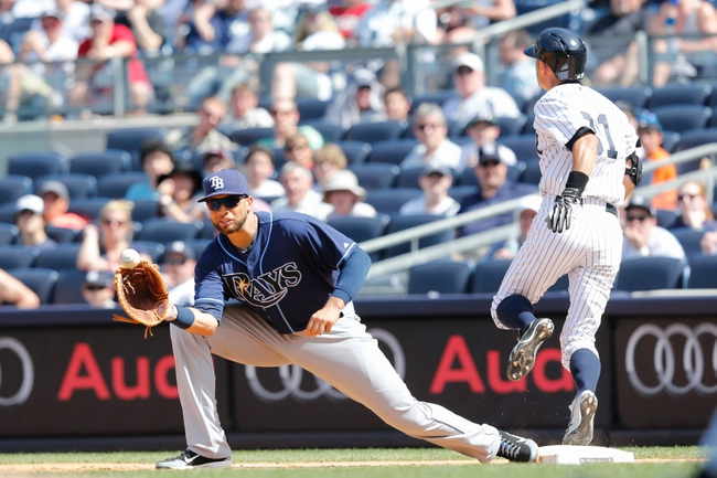 Jun 23, 2013; Bronx, NY, USA;  New York Yankees right fielder Ichiro Suzuki (31) steps to first as Tampa Bay Rays first baseman James Loney (21) is late with the tag during the fifth inning at Yankee Stadium.  Mandatory Credit: Anthony Gruppuso-USA TODAY Sports