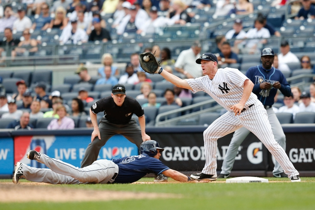 Jun 23, 2013; Bronx, NY, USA; Tampa Bay Rays second baseman Ben Zobrist (18) slides back to first as New York Yankees first baseman Lyle Overbay (55) is late with the tag during the ninth inning at Yankee Stadium.  Tampa won 3-1.  Mandatory Credit: Anthony Gruppuso-USA TODAY Sports