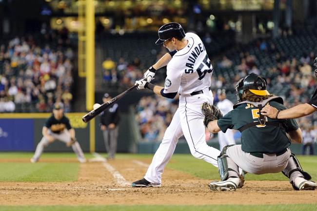 Jun 23, 2013; Seattle, WA, USA; Seattle Mariners left fielder Michael Saunders (55) hits a single against the Oakland Athletics during the 10th inning at Safeco Field. Seattle defeated Oakland 6-3. Mandatory Credit: Steven Bisig-USA TODAY Sports