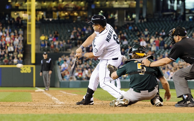 Jun 23, 2013; Seattle, WA, USA; Seattle Mariners designated hitter Kendrys Morales (8) hits the game winning 3-run home run against the Oakland Athletics during the 10th inning at Safeco Field. Seattle defeated Oakland 6-3. Mandatory Credit: Steven Bisig-USA TODAY Sports