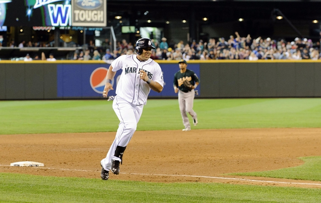 Jun 23, 2013; Seattle, WA, USA; Seattle Mariners designated hitter Kendrys Morales (8) rounds 3rd base after hitting the game winning 3-run home run against the Oakland Athletics during the 10th inning at Safeco Field. Seattle defeated Oakland 6-3. Mandatory Credit: Steven Bisig-USA TODAY Sports