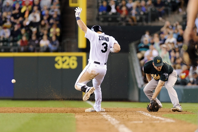 Jun 23, 2013; Seattle, WA, USA; Seattle Mariners catcher Mike Zunino (3) reaches 1st base on a wild pitch during the 10th inning at Safeco Field. Seattle defeated Oakland 6-3. Mandatory Credit: Steven Bisig-USA TODAY Sports
