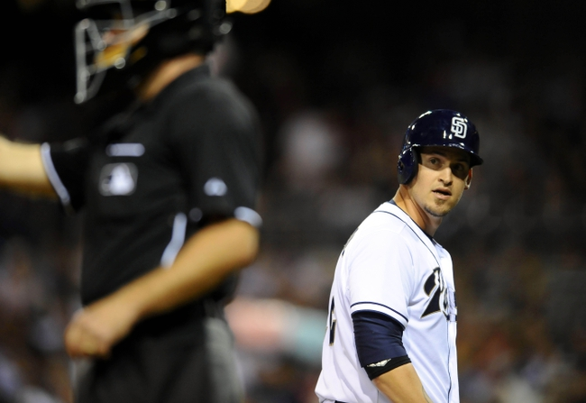 June 25, 2013; San Diego, CA, USA; San Diego Padres catcher Yasmani Grandal (12) reacts to a called strike three by home plate umpire Ed Hickox (left) during the sixth inning against the Philadelphia Phillies at Petco Park.  Mandatory Credit: Christopher Hanewinckel-USA TODAY Sports