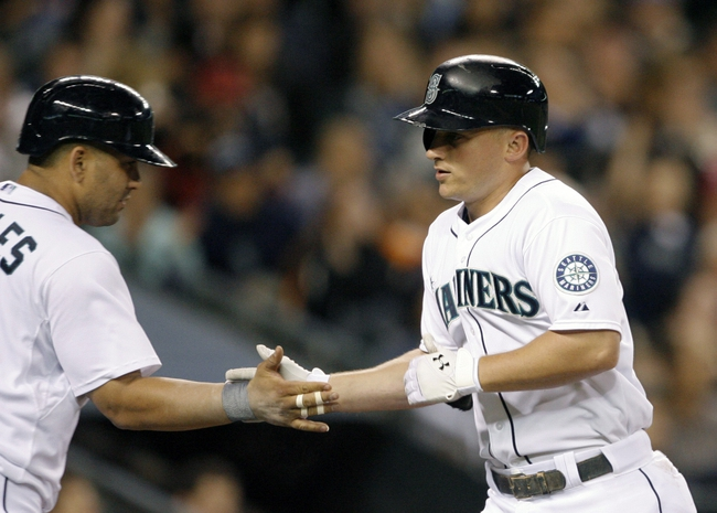 Jun 25, 2013; Seattle, WA, USA; Seattle Mariners third baseman Kyle Seager (15) is greeted by designated hitter Kendrys Morales (8) after hitting a solo-home run against the Pittsburgh Pirates during the sixth inning at Safeco Field. Mandatory Credit: Joe Nicholson-USA TODAY Sports