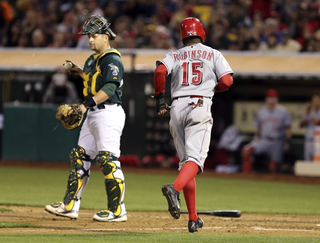 Jun 25, 2013; Oakland, CA, USA; Cincinnati Reds left fielder Derrick Robinson (15) is walked in for a run ahead of Oakland Athletics catcher Stephen Vogt (21) during the fifth inning at O.co Coliseum. The Oakland Athletics defeated the Cincinnati Reds 7-3. Mandatory Credit: Kelley L Cox-USA TODAY Sports