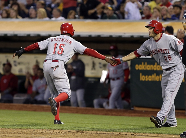 Jun 25, 2013; Oakland, CA, USA; Cincinnati Reds left fielder Derrick Robinson (15) celebrates with left fielder Chris Heisey (28) after being walked in for a run against the Oakland Athletics during the fifth inning at O.co Coliseum. The Oakland Athletics defeated the Cincinnati Reds 7-3. Mandatory Credit: Kelley L Cox-USA TODAY Sports