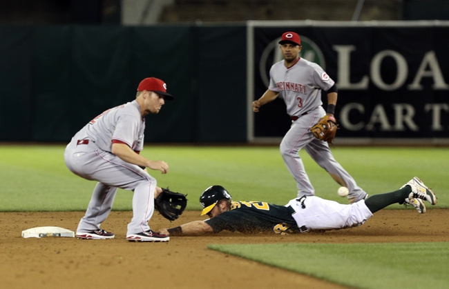 Jun 25, 2013; Oakland, CA, USA; Oakland Athletics second baseman Eric Sogard (28) steals second base against Cincinnati Reds shortstop Zack Cozart (2) during the sixth inning at O.co Coliseum. The Oakland Athletics defeated the Cincinnati Reds 7-3. Mandatory Credit: Kelley L Cox-USA TODAY Sports