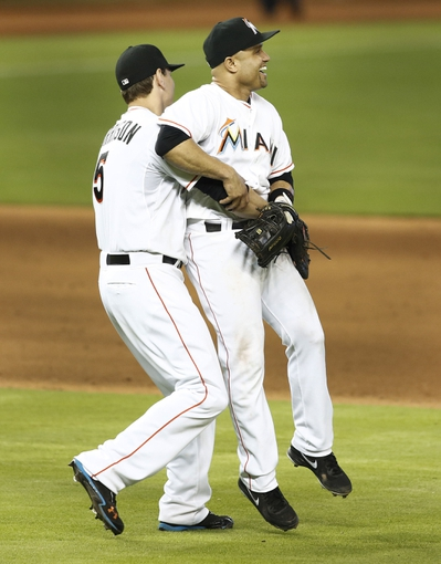 Jun 26, 2013; Miami, FL, USA;  Miami Marlins first baseman Logan Morrison (left) lifts third baseman Placido Polanco (30) against the Minnesota Twins at Marlins Park. The Marlins won 5-3. Mandatory Credit: Robert Mayer-USA TODAY Sports