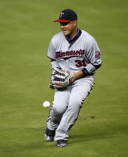 Jun 26, 2013; Miami, FL, USA; Minnesota Twins left fielder Oswaldo Arcia (31) bobbles the ball on a base hit by Miami Marlins starting pitcher Kevin Slowey (not pictured) in the fifth inning at Marlins Park. The Marlins won 5-3. Mandatory Credit: Robert Mayer-USA TODAY Sports