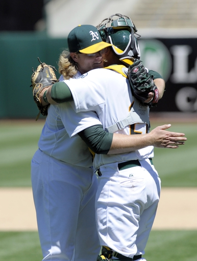Jun 26, 2013; Oakland, CA, USA; Oakland Athletics starting pitcher A.J. Griffin (64) hugs catcher Stephen Vogt (21) after throwing a complete game against the Cincinnati Reds at O.Co Coliseum. The Oakland Athletics defeated the Cincinnati Reds 5-0. Mandatory Credit: Ed Szczepanski-USA TODAY Sports