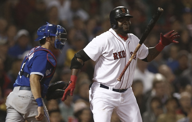 Jun 27, 2013; Boston, MA, USA;  Boston Red Sox player David Ortiz reacts to striking out as Toronto Blue Jays catcher J.P. Arencibia heads for the dugout during the seventh inning at Fenway Park. Mandatory Credit: Winslow Townson-USA TODAY Sports