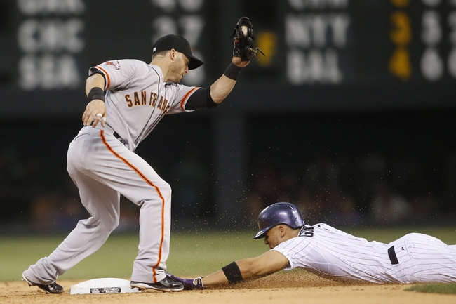 Jun 28, 2013; Denver, CO, USA; Colorado Rockies left fielder Carlos Gonzalez (right) steals second base before San Francisco Giants second baseman Marco Scutaro (left) can make the tag during the fourth inning at Coors Field. Mandatory Credit: Chris Humphreys-USA TODAY Sports
