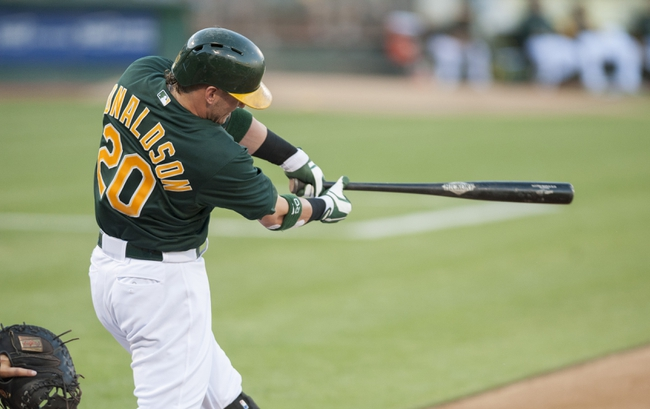 Jun 28, 2013; Oakland, CA, USA; Oakland Athletics third baseman Josh Donaldson (20) hits an RBI single during the second inning against the St. Louis Cardinals at O.Co Coliseum. Mandatory Credit: Ed Szczepanski-USA TODAY Sports