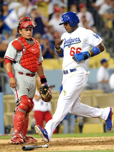 Jun 28, 2013; Los Angeles, CA, USA;  Philadelphia Phillies catcher Carlos Ruiz (51) looks on as Los Angeles Dodgers right fielder Yasiel Puig (66) scores a run in the sixth inning of the game at Dodger Stadium. Mandatory Credit: Jayne Kamin-Oncea-USA TODAY Sports
