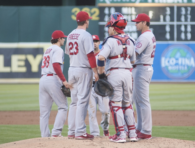 Jun 28, 2013; Oakland, CA, USA; St. Louis Cardinals shortstop Pete Kozma (38) and third baseman David Freese (23) and catcher Yadier Molina (4) and manager Mike Matheny (22) and second baseman Matt Carpenter (13) meet at the mound during the second inning of the game against the Oakland Athletics at O.Co Coliseum. Mandatory Credit: Ed Szczepanski-USA TODAY Sports
