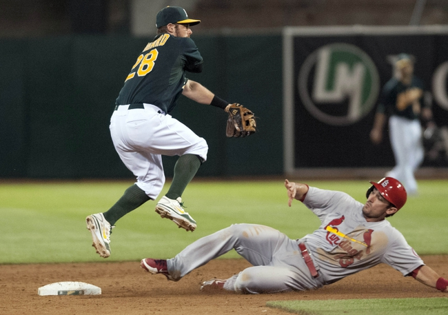 Jun 28, 2013; Oakland, CA, USA; Oakland Athletics second baseman Eric Sogard (28) attempts to turn a double play as St. Louis Cardinals second baseman Matt Carpenter (13) slides into second base at O.Co Coliseum. Mandatory Credit: Ed Szczepanski-USA TODAY Sports