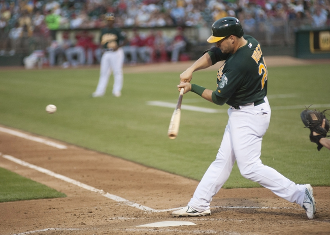 Jun 28, 2013; Oakland, CA, USA; Oakland Athletics catcher Stephen Vogt (21) hits a home run during the fourth inning of the game against the St. Louis Cardinals at O.Co Coliseum. The Oakland Athletics defeated the St. Louis Cardinals 6-1. Mandatory Credit: Ed Szczepanski-USA TODAY Sports