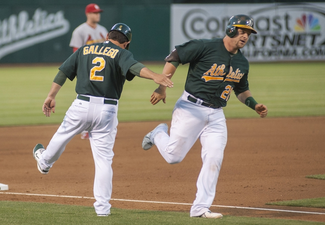 Jun 28, 2013; Oakland, CA, USA; Oakland Athletics third base coach Mike Gallego (2) congratulates catcher Stephen Vogt (21) after he hit a home run during the fourth inning against the St. Louis Cardinals at O.Co Coliseum. The Oakland Athletics defeated the St. Louis Cardinals 6-1. Mandatory Credit: Ed Szczepanski-USA TODAY Sports