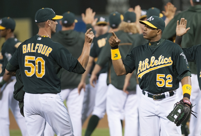 Jun 28, 2013; Oakland, CA, USA; Oakland Athletics relief pitcher Grant Balfour (50) and left fielder Yoenis Cespedes (52) celebrate after defeating the St. Louis Cardinals at O.Co Coliseum. The Oakland Athletics defeated the St. Louis Cardinals 6-1. Mandatory Credit: Ed Szczepanski-USA TODAY Sports