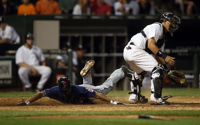 Jun 28, 2013; Chicago, IL, USA; Cleveland Indians center fielder Michael Bourn (left) scores a run past Chicago White Sox catcher Hector Gimenez in the 9th inning of the second game of a baseball doubleheader at US Cellular Field. Mandatory Credit: Jerry Lai-USA TODAY Sports
