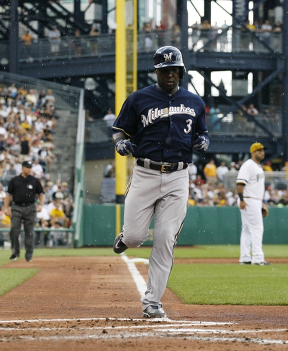 Jun 30, 2013; Pittsburgh, PA, USA; Milwaukee Brewers third baseman Yuniesky Betancourt (3) crosses home plate to score a run against the Pittsburgh Pirates during the second inning at PNC Park. Mandatory Credit: Charles LeClaire-USA TODAY Sports