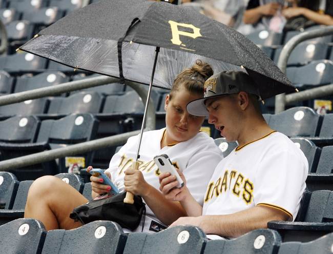 Jun 30, 2013; Pittsburgh, PA, USA; Pittsburgh Pirates fans Ashley Nardick (left) and George Haldeman (right) looks at the weather forecast on their smartphones during a rain delay in the second inning between the Milwaukee Brewers and the Pittsburgh Pirates at PNC Park. Mandatory Credit: Charles LeClaire-USA TODAY Sports