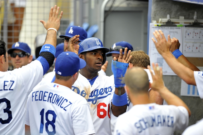 June 30, 2013; Los Angeles, CA, USA; Los Angeles Dodgers right fielder Yasiel Puig (66) is congratulated after scoring a run in the third inning against the Philadelphia Phillies at Dodger Stadium. Mandatory Credit: Gary A. Vasquez-USA TODAY Sports