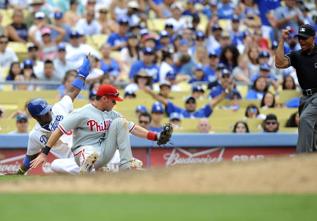 June 30, 2013; Los Angeles, CA, USA; Los Angeles Dodgers right fielder Yasiel Puig (66) is caught stealing third during the seventh inning against the tag of Philadelphia Phillies third baseman Michael Young (10) at Dodger Stadium. Mandatory Credit: Gary A. Vasquez-USA TODAY Sports
