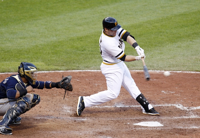 Jun 30, 2013; Pittsburgh, PA, USA; Pittsburgh Pirates pinch hitter Russell Martin (55) hits a game winning RBI single against the Milwaukee Brewers during the fourteenth inning at PNC Park. The Pittsburgh Pirates won 2-1 in fourteen innings. Mandatory Credit: Charles LeClaire-USA TODAY Sports