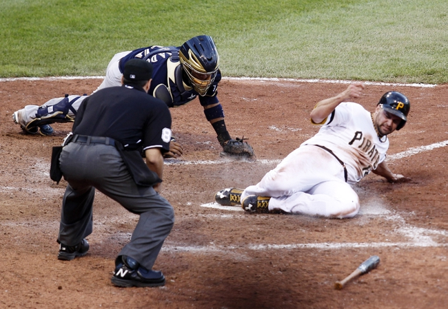 Jun 30, 2013; Pittsburgh, PA, USA; Pittsburgh Pirates first baseman Gaby Sanchez (14) slides across home plate with the game winning run as Milwaukee Brewers catcher Martin Maldonado (12) misses the tag during the fourteenth inning at PNC Park. The Pittsburgh Pirates won 2-1 in fourteen innings. Mandatory Credit: Charles LeClaire-USA TODAY Sports