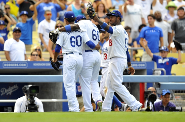 June 30, 2013; Los Angeles, CA, USA; Los Angeles Dodgers relief pitcher Jose Dominguez (60) is congratulated by right fielder Yasiel Puig (66) and shortstop Hanley Ramirez (13) after pitching the eighth inning against the Philadelphia Phillies at Dodger Stadium. Mandatory Credit: Gary A. Vasquez-USA TODAY Sports