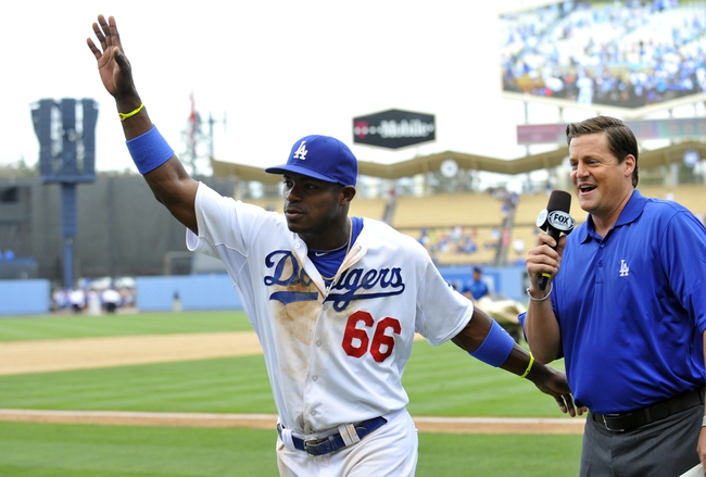 June 30, 2013; Los Angeles, CA, USA; Los Angeles Dodgers right fielder Yasiel Puig (66) acknowledges fans following the 6-1 victory against the Philadelphia Phillies at Dodger Stadium. Mandatory Credit: Gary A. Vasquez-USA TODAY Sports