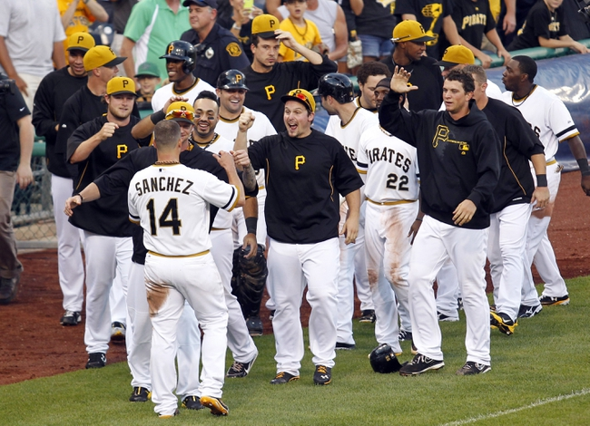 Jun 30, 2013; Pittsburgh, PA, USA; Pittsburgh Pirates first baseman Gaby Sanchez (14) is congratulated by teammates after Sanchez scored the game winning run against the Milwaukee Brewers during the fourteenth inning at PNC Park. The Pittsburgh Pirates won 2-1 in fourteen innings. Mandatory Credit: Charles LeClaire-USA TODAY Sports