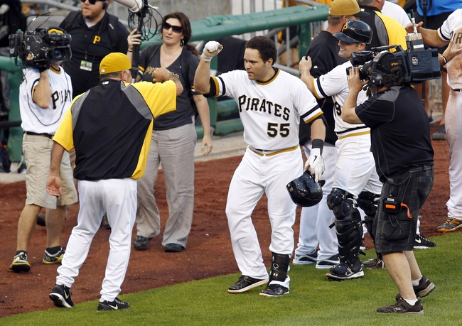Jun 30, 2013; Pittsburgh, PA, USA; Pittsburgh Pirates third base coach Nick Leyva (left) high fives Pirates pinch hitter Russell Martin after Martin hit a game winning RBI single against the Milwaukee Brewers during the fourteenth inning at PNC Park. The Pittsburgh Pirates won 2-1 in fourteen innings. Mandatory Credit: Charles LeClaire-USA TODAY Sports