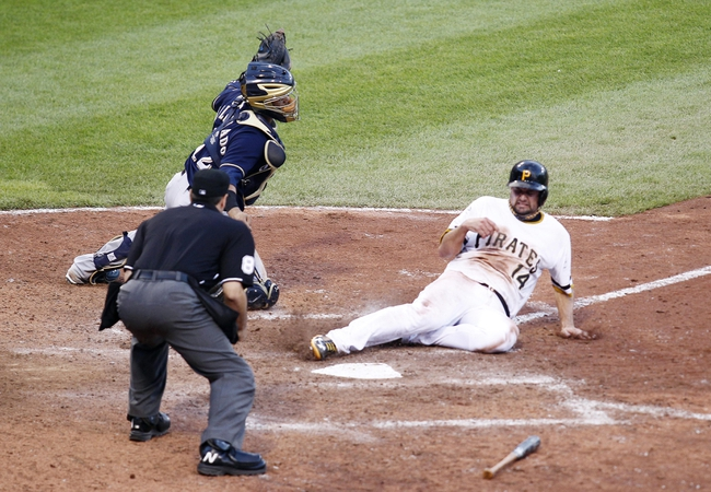Jun 30, 2013; Pittsburgh, PA, USA; Pittsburgh Pirates first baseman Gaby Sanchez (14) slides across home plate with the game winning run as Milwaukee Brewers catcher Martin Maldonado (12) attempts a tag during the fourteenth inning at PNC Park. The Pittsburgh Pirates won 2-1 in fourteen innings. Mandatory Credit: Charles LeClaire-USA TODAY Sports