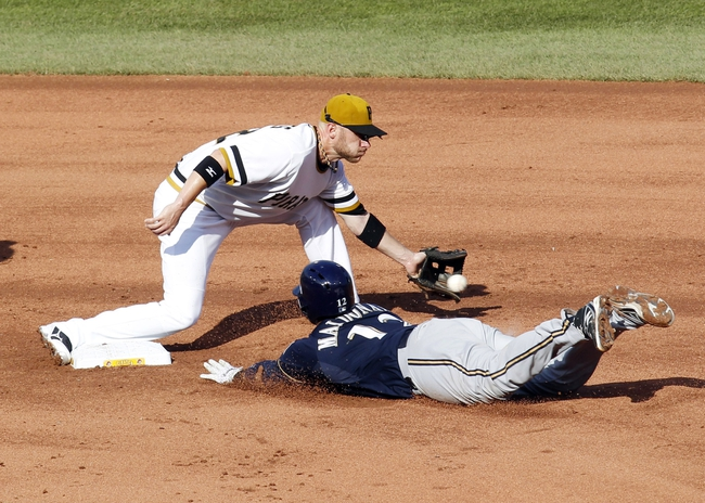 Jun 30, 2013; Pittsburgh, PA, USA; Milwaukee Brewers catcher Martin Maldonado (12) slides into second base with a double as Pittsburgh Pirates shortstop Clint Barmes (top) takes the throw during the eighth inning at PNC Park. The Pittsburgh Pirates won 2-1 in fourteen innings. Mandatory Credit: Charles LeClaire-USA TODAY Sports