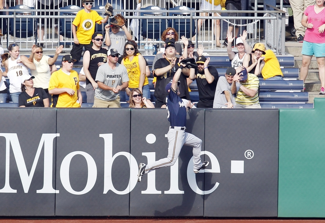 Jun 30, 2013; Pittsburgh, PA, USA; Milwaukee Brewers left fielder Logan Schafer (22) makes a leaping catch at the wall to take a home run away from Pittsburgh Pirates first baseman Gaby Sanchez (not pictured) during the seventh inning at PNC Park. The Pittsburgh Pirates won 2-1 in fourteen innings.. Mandatory Credit: Charles LeClaire-USA TODAY Sports