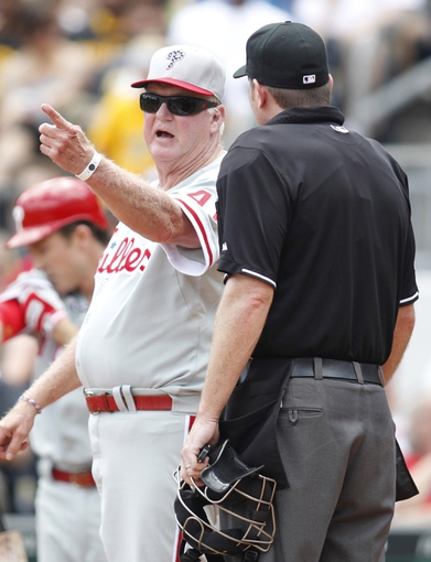 Jul 4, 2013; Pittsburgh, PA, USA; Philadelphia Phillies manager Charlie Manuel (41) gestures as he talks to home plate umpire Chris Conroy (right) against the Pittsburgh Pirates during the fifth inning at PNC Park. The Philadelphia Phillies won 6-4. Mandatory Credit: Charles LeClaire-USA TODAY Sports