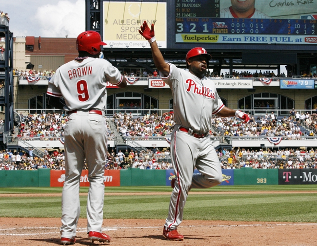 Jul 4, 2013; Pittsburgh, PA, USA; Philadelphia Phillies left fielder Domonic Brown (9) and right fielder Delmon Young (right) celebrate after both scored on a single by catcher Carlos Ruiz (not pictured) against the Pittsburgh Pirates during the sixth inning at PNC Park. The Philadelphia Phillies won 6-4. Mandatory Credit: Charles LeClaire-USA TODAY Sports