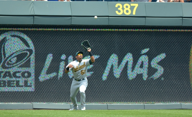 Jul 7, 2013; Kansas City, MO, USA; Oakland Athletics left fielder Yoenis Cespedes (52) makes the catch on a long fly ball to left field in the first inning of the game against the Kansas City Royals at Kauffman Stadium. Mandatory Credit: Denny Medley-USA TODAY Sports