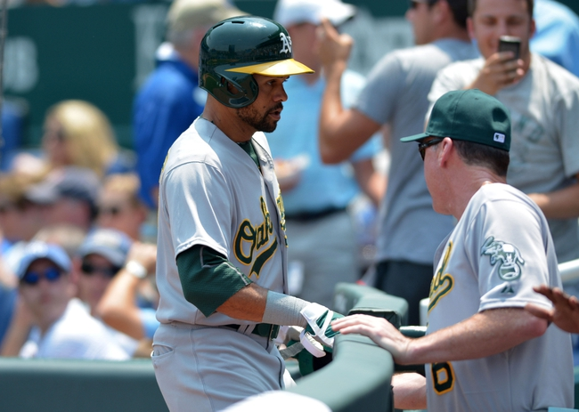 Jul 7, 2013; Kansas City, MO, USA; Oakland Athletics center fielder Coco Crisp (4) is congratulated by manager Bob Melvin (6) after scoring in the second inning of the game against the Kansas City Royals at Kauffman Stadium. Mandatory Credit: Denny Medley-USA TODAY Sports