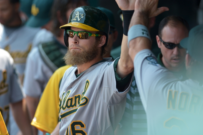 Jul 7, 2013; Kansas City, MO, USA; Oakland Athletics right fielder Josh Reddick (16) is congratulated in the dugout after scoring in the second inning of the game against the Kansas City Royals at Kauffman Stadium. Mandatory Credit: Denny Medley-USA TODAY Sports
