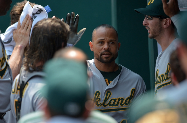 Jul 7, 2013; Kansas City, MO, USA; Oakland Athletics center fielder Coco Crisp (4) is congratulated in the dugout after scoring in the second inning of the game against the Kansas City Royals at Kauffman Stadium. Mandatory Credit: Denny Medley-USA TODAY Sports
